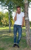 Mladý muž v parku na mobilní telefon