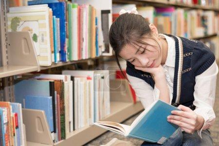 Woman reading a book near bookshelf