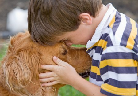 Photo pour Petit garçon étreignant chien - image libre de droit