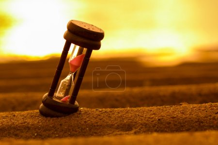 Photo for Closeup of hourglass on the sand.Timer Beach Sunrise - Royalty Free Image