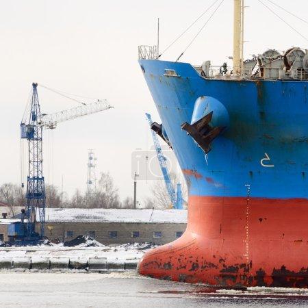 Cargo ship's bow heading forward against port cranes