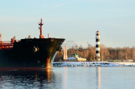 Cargo ship's bow heading forward against a lighthouse