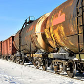 Grunge cargo train on the move in winter