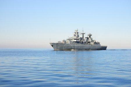 Grey modern warship sailing in still water...