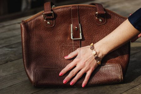 Female hand with bracelet holds a brown leather bag