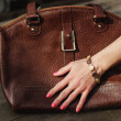 Female hand with bracelet holds a brown leather ba...