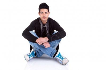 Foto de Joven guapo, sentado en el suelo, relajado y confiado. Estudio sobre fondo blanco . - Imagen libre de derechos