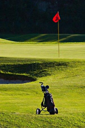 Photo pour Sac de golf près du golf vert, avec poteau et drapeau rouge - image libre de droit