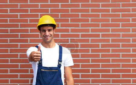Young worker showing tumb up in front of a brick wall