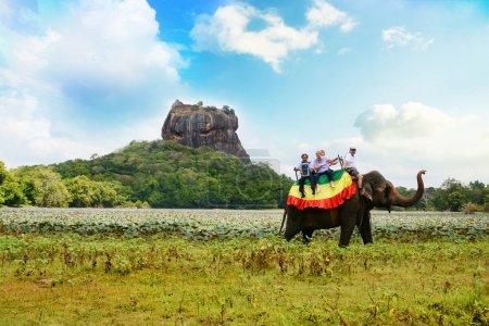 Photo for Tourists on an elephant ride tour near the giant Sigiriya Rock Fortress in Sri Lanka - Royalty Free Image