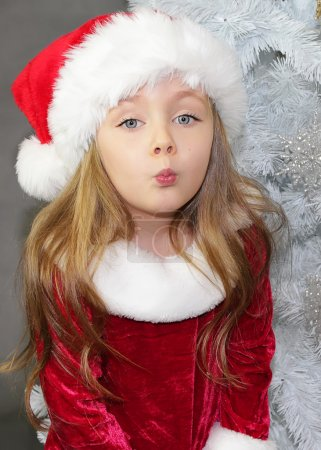 Girl in red dressed as Santa Claus with Christmas tree
