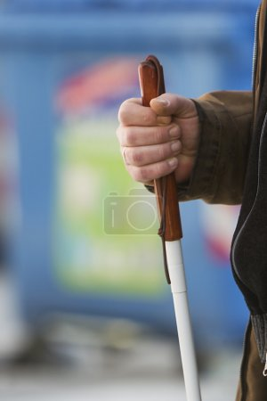 Close up in blind man's hands holding a stick