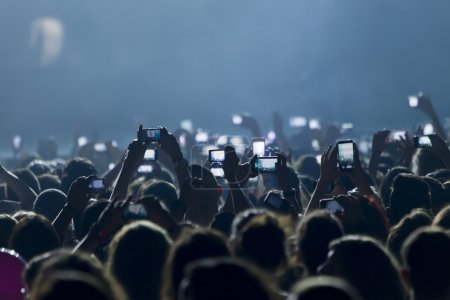 Photo for THESSALONIKI, GREECE, MAY 8 2014:People taking photographs with touch smart phone during a music concert live on stage for the Ace of Heart tour at Sports arena in Thessaloniki. - Royalty Free Image