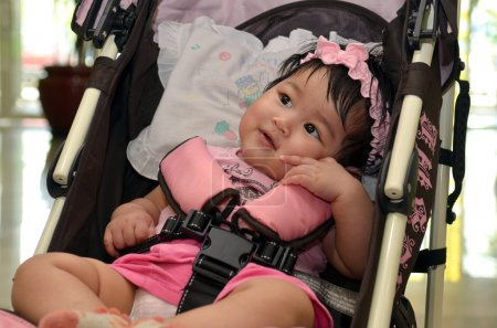 Cute Asian baby girl smiling while sitting in her stroller