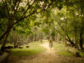 Young Woman Walking on Mysterious Path into Enchanted Forest