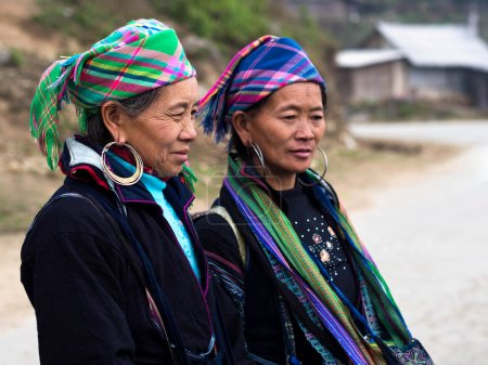 Two Hmong women wearing traditional attire and jew...