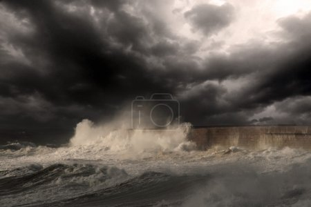 Photo for Dramatic sea scene with big white waves crashing against the harbor wall of Leixoes, near Porto in Portugal Enhanced sky. Added a little digital grain - Royalty Free Image