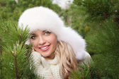 Girl with toothy smile in winter fir forest