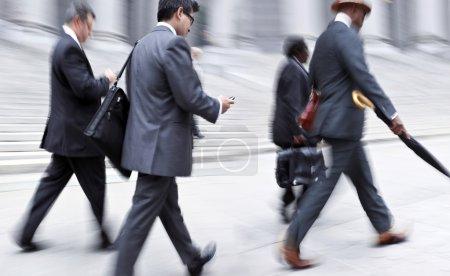 Photo pour Gens d'affaires aux heures de pointe, marchant dans la rue, dans le style de motion blur - image libre de droit