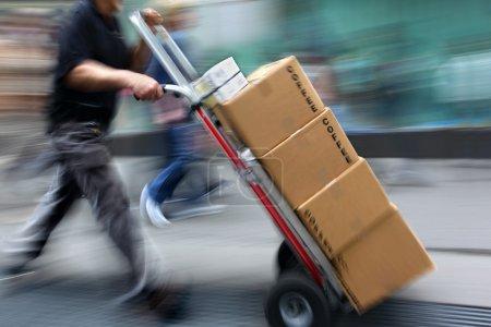 Photo pour Marchandises de livraison avec chariot à la main, volontairement flou de mouvement. - image libre de droit