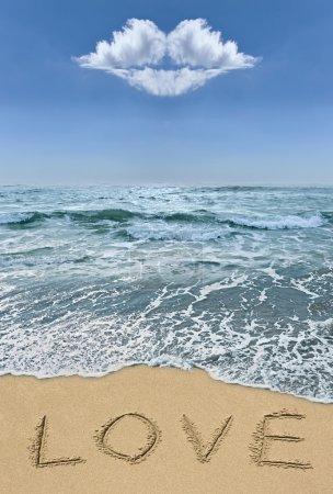 Photo pour Amour signe dans le sable sur la plage avec des nuages sous la forme d'un baiser. romantique élément de design. - image libre de droit