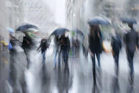 Photo pour Les gens d'affaires marchant dans la rue par un mouvement de jour de pluie floue - image libre de droit