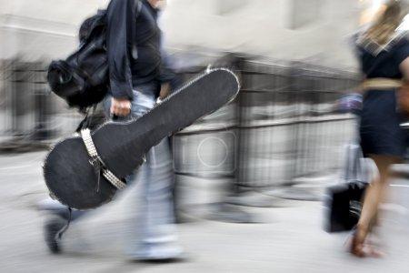 Photo pour Homme dans une rue de flou de mouvement avec un instrument de musique - image libre de droit