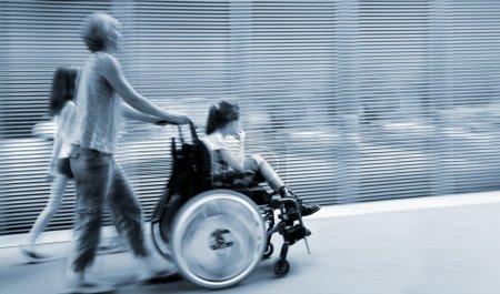 Photo pour Image abstraite de l'enfant handicapé en fauteuil roulant accompagné et style moderne avec un arrière-plan flou dans la tonalité bleue - image libre de droit