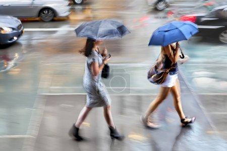 Photo pour Personnes marchant dans la rue, sur une motion de jour de pluie floue - image libre de droit