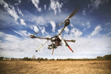 Photo for Flying drone is filming video in the blue sky - Royalty Free Image