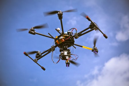 Photo for Flying helicopter drone is filming video in the blue sky - Royalty Free Image