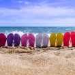 Line of brightly colored flip flops arranged in a ...