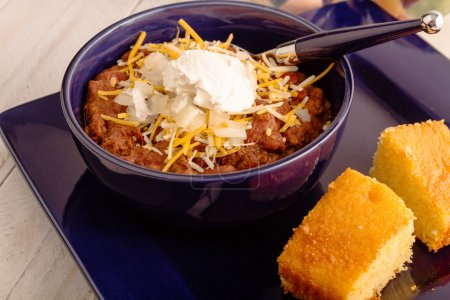 Photo for Blue dinner plate with bowl of elk meat chili with onions, sour cream and shredded cheese - Royalty Free Image