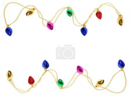 Photo pour Une guirlande de lumières de Noël bordure or perles forme haut et en bas sur fond blanc - image libre de droit