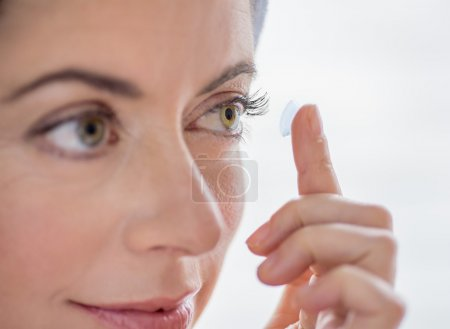 Photo for Close up of an attractive mature lady putting on contact lenses in her green eyes - Royalty Free Image