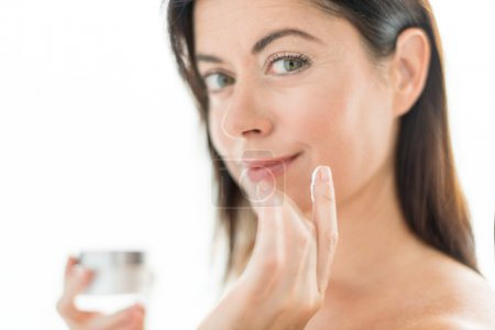 Woman in her forties applying face cream