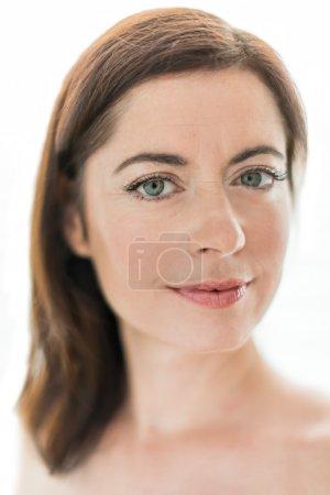 Photo pour Portrait d'une mystérieuse dame mûre regardant la caméra - image libre de droit