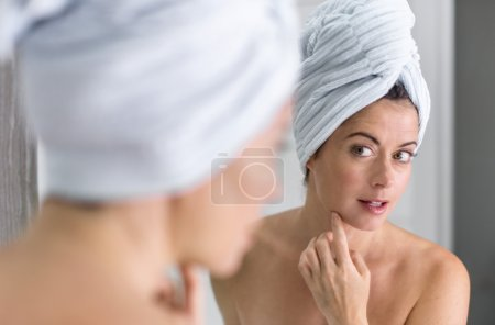 Middle aged woman looking in the mirror