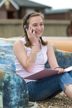 Teenage girl sitting on beach using phone laughing