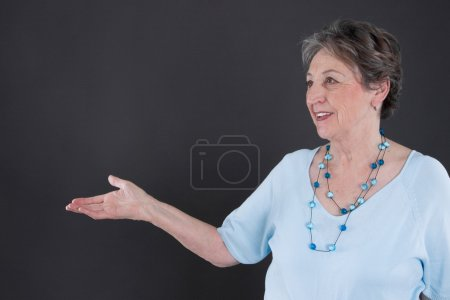 Photo for Older gray haired lady advertises something - Royalty Free Image