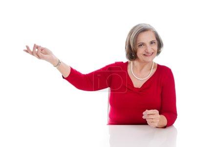 Photo pour Femme mûre en rouge fait de la publicité. Femme âgée présentant quelque chose - image libre de droit