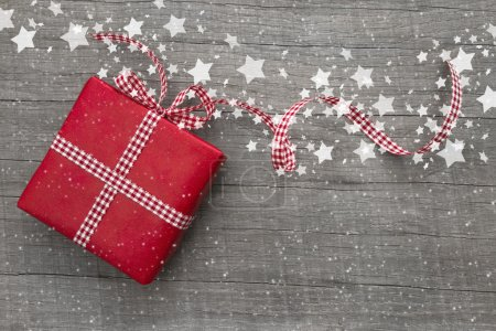 Christmas Present wrapped in red paper on a wooden background for a greeting card