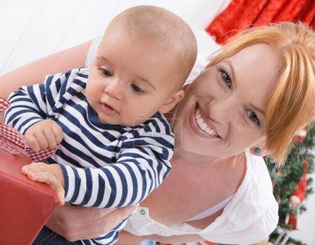 Photo pour Amour inconditionnel - mère et bébé ouverture d'un Noël ou cadeau - héhé - image libre de droit