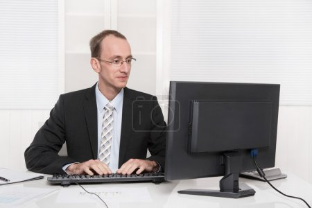 Satisfied conscientious businessman at his office in tie and suit
