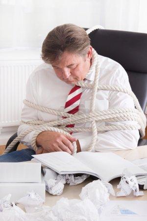 Photo pour Travailler sans fin. Homme d'affaires fatigué attaché à la corde - image libre de droit