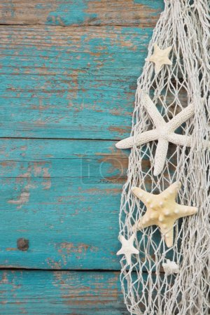 Starfish in a fishing net with a turquoise wooden background, po