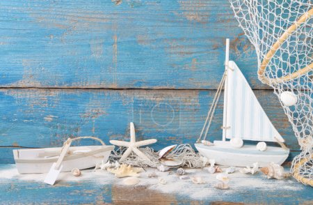 Photo for Starfish and shells with toy boats and a blue wooden background - Royalty Free Image