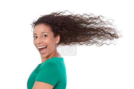 Photo pour Joyeux jeune femme - ses cheveux soufflant dans le vent dans une chemise verte aux cheveux longs . - image libre de droit