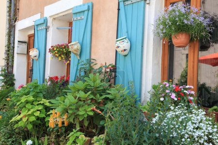 Flowers and plants decorating house exterior.