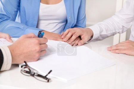 Photo pour Conseiller financier explique un contrat - jeune couple. mains - jeune marié couple dans une réunion d'affaires - image libre de droit